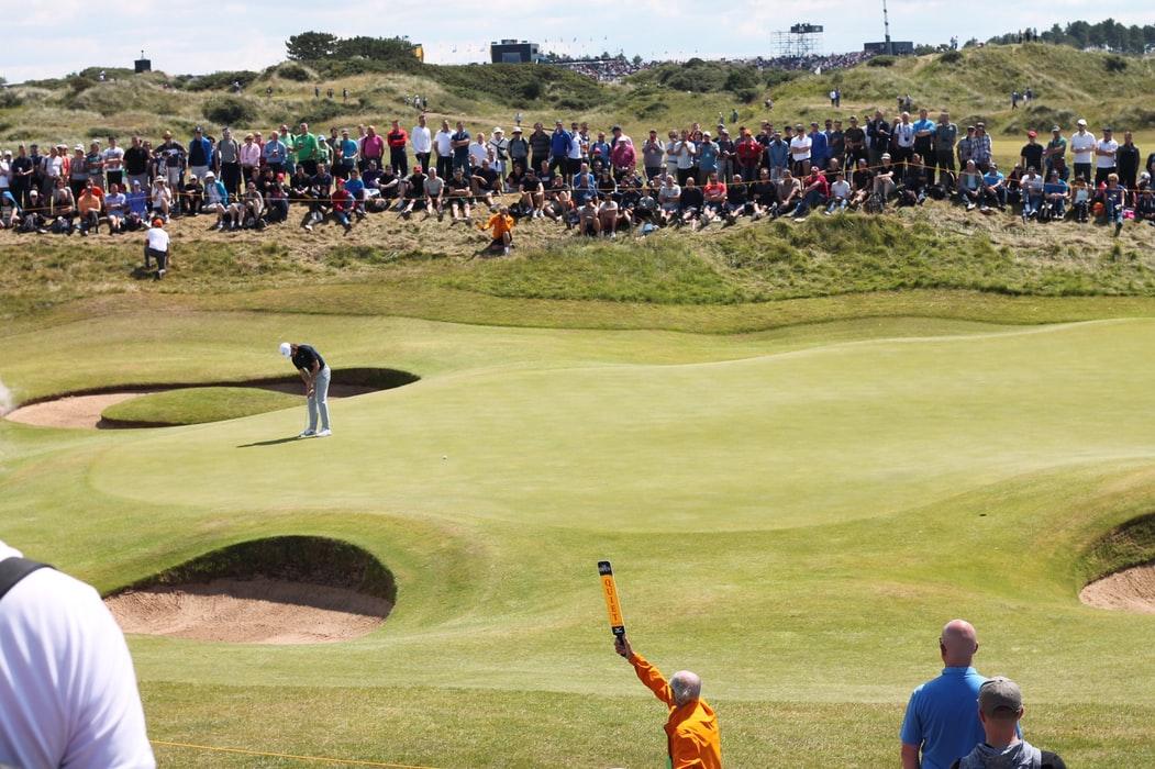 Olika personer trängs på samma golfbana